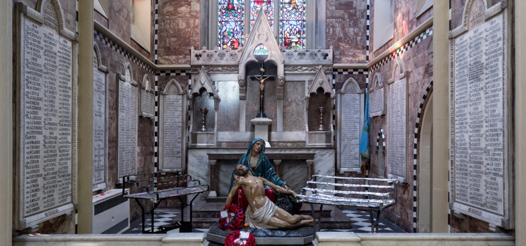 Image of the WW1 memorial chapel with alter, statue of Our Lady holding her son after he has been taken down from the cross with the names of all soldiers from the Diocese adorning the walls of the chapel.