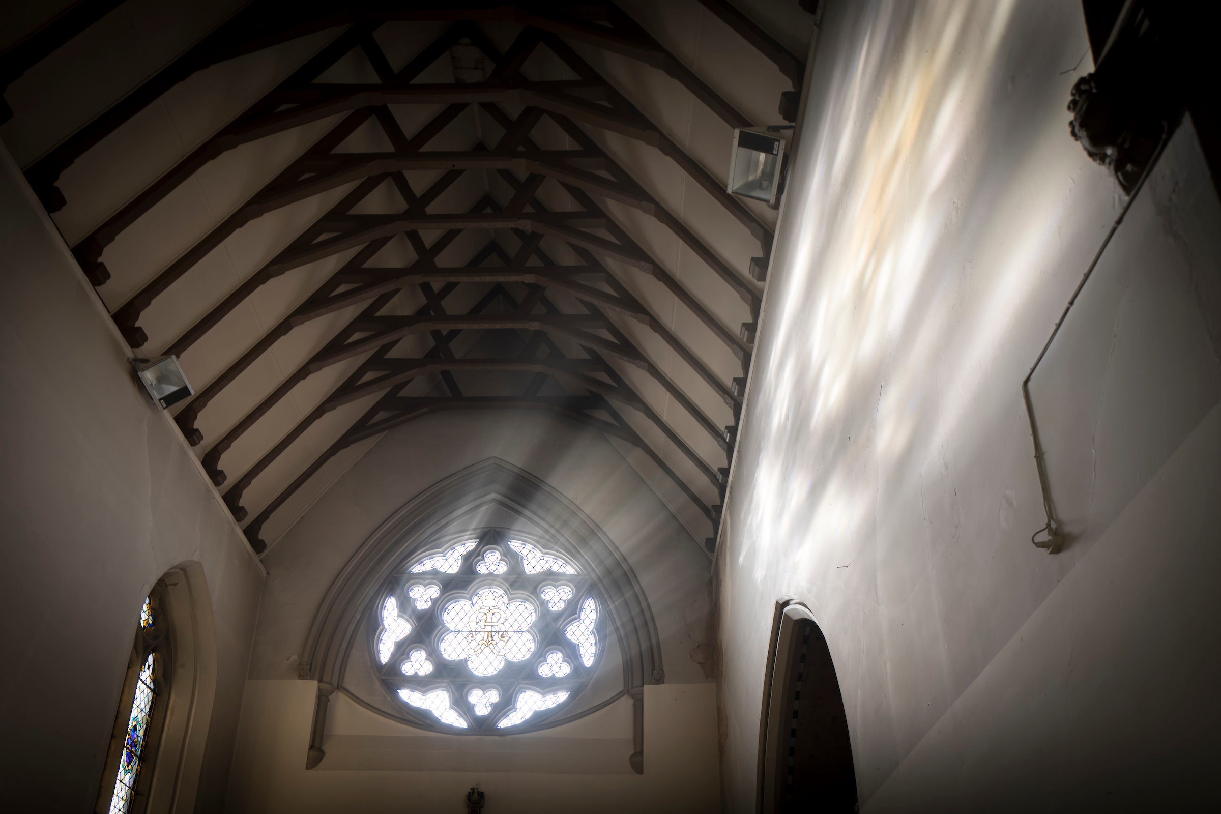 A Photograph of sun rays shining through the star shaped stained glass window int he upper chapelA Photograph of sun rays shining thruogh the star shaped stained glass window int he upper chapel