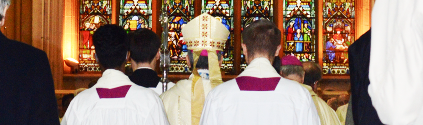 Bishop John Arnold and servers gather in front of the west window